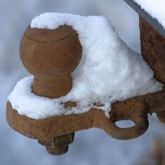a rusty, snow-covered trailer hitch