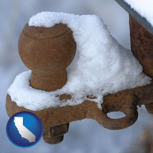 a rusty, snow-covered trailer hitch - with California icon