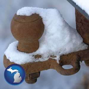 a rusty, snow-covered trailer hitch - with Michigan icon