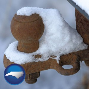 a rusty, snow-covered trailer hitch - with North Carolina icon