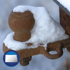 a rusty, snow-covered trailer hitch - with North Dakota icon