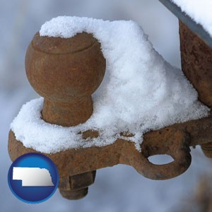 a rusty, snow-covered trailer hitch - with Nebraska icon