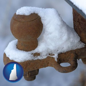 a rusty, snow-covered trailer hitch - with New Hampshire icon
