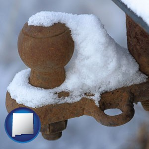 a rusty, snow-covered trailer hitch - with New Mexico icon