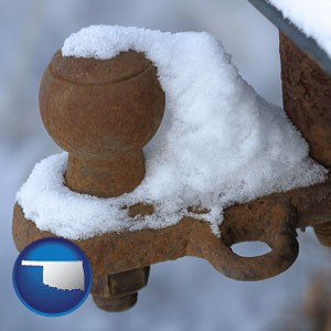 a rusty, snow-covered trailer hitch - with Oklahoma icon