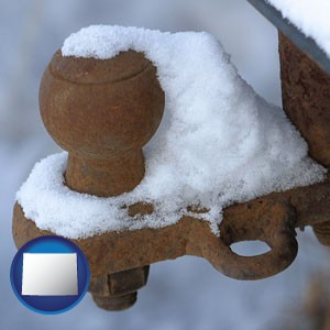 a rusty, snow-covered trailer hitch - with Wyoming icon